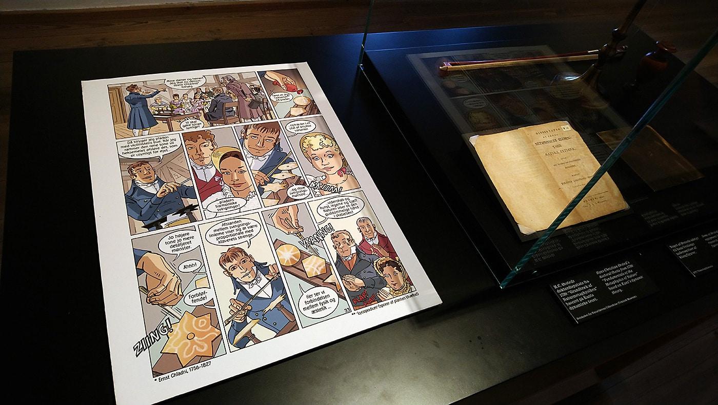 """Foto fra H.C. Ørsteds-udstillingen i Rundetaarn, hvor tegneserien """"Ørsted – Han satte strøm til verden"""" har fået en fornem plads som en del af udstillingen, hvor Ørsteds klangplader vises."""